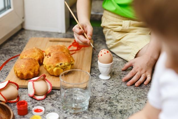 Zwei kinder ostern vorbereitung durch malen von ostereiern und feiertagsdekorationen zu hause