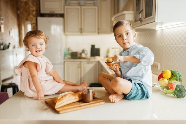 Zwei kinder schmieren geschmolzene schokolade auf brot, leckere sandwiches.