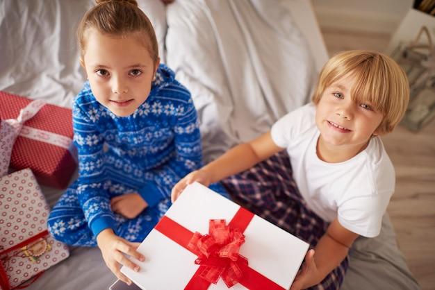 Zwei kinder sitzen auf bett mit weihnachtsgeschenk