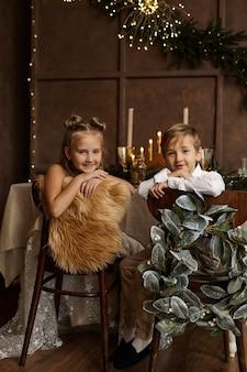 Zwei kinder sitzen auf stühlen neben einem festlichen tisch