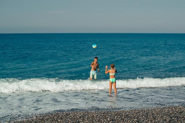 Zwei kinder spielen ball am strand