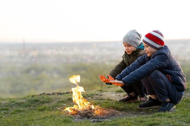 Zwei kinder spielen bei kaltem wetter mit feuer im freien.