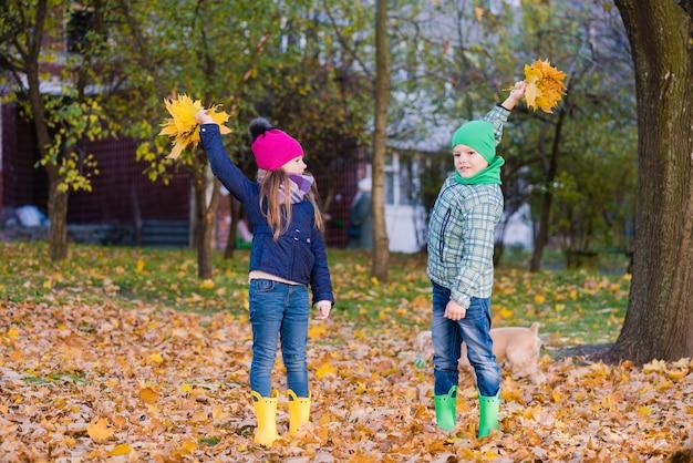 Zwei kinder spielen mit ahornblättern im park