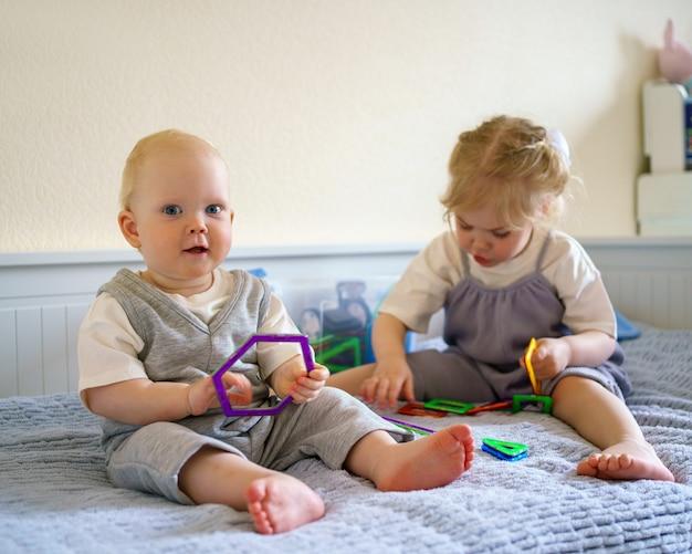 Zwei kinder spielen mit magnetischem bauspielzeug, während sie auf dem bett sitzen