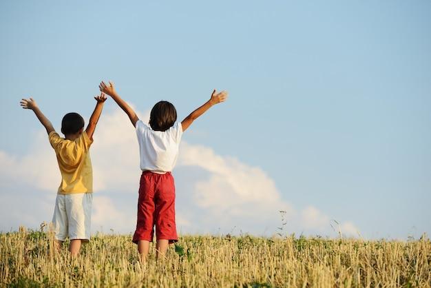 Zwei kinder stehen auf der wiese mit erhobenen armen in der luft