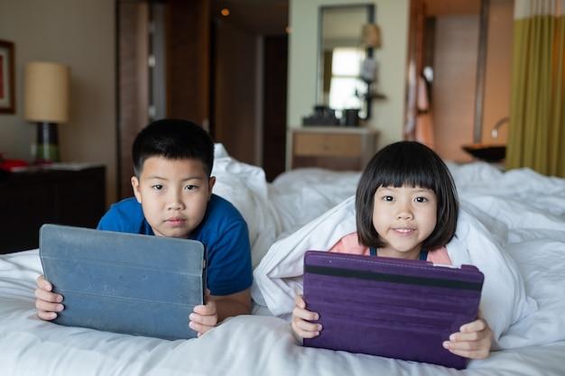 Zwei kinder süchtig tablette, asiatisches kind beobachten cartoon