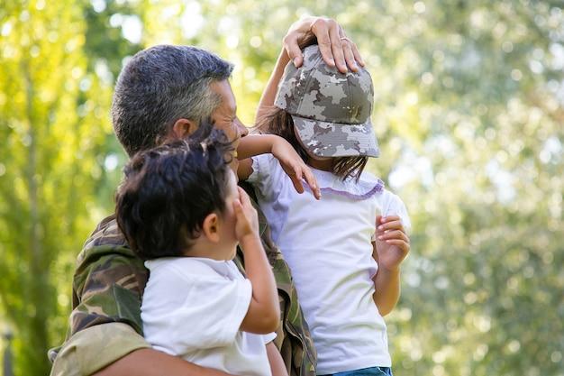 Zwei kinder treffen militärvater in uniform im freien. vater hält kinder in den armen und zieht mädchen in tarnkappe an. familientreffen oder rückkehr nach hause konzept