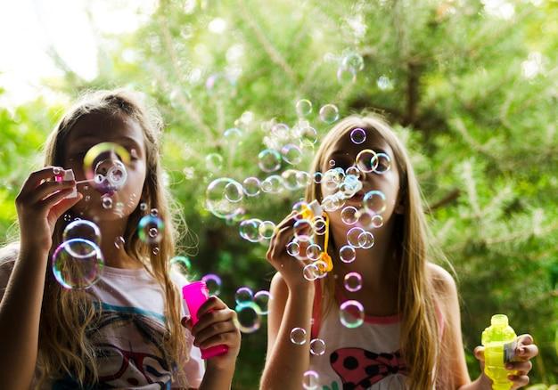 Zwei kinderfreundinnen spielen mit wasser ballons im freien. viel spaß bei aktivitäten in der kindheit.