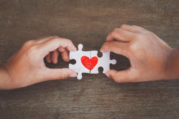 Zwei kinderhände, die paarpuzzlestück mit gezogenem rotem herzen verbinden