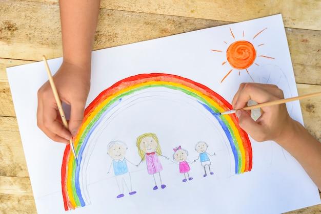 Zwei kinderhände zeichnen eine zeichnung mit einem pinsel und farben. ansicht von oben