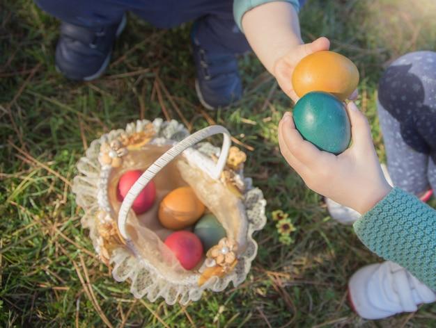 Zwei kinderhanddetail zeigen ihre ostereier, bevor sie in den korb auf den garten gesetzt werden