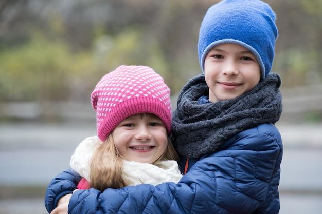 Zwei kinderjunge und -mädchen, die draußen tragen warme kleidung im kalten herbst- oder winterwetter sich umarmen.