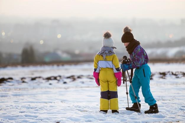 Zwei kinderjunge und -mädchen, die spaß draußen im winter spielt mit fotokamera auf einem stativ auf schnee haben, umfassten feld.