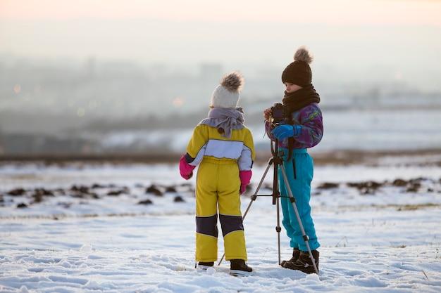 Zwei kinderjungen und -mädchen, die spaß draußen im winter haben