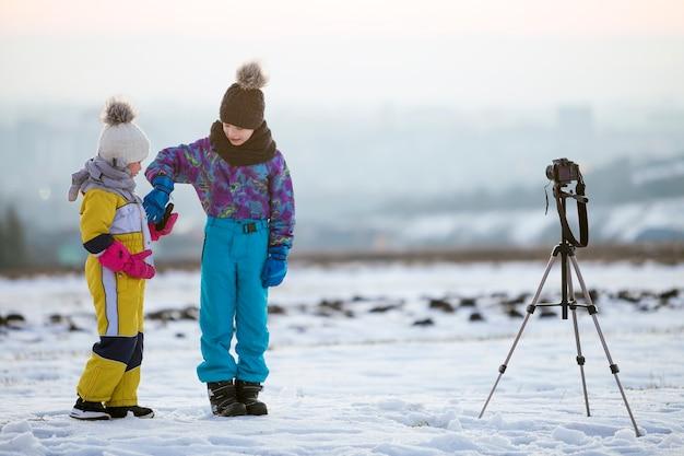 Zwei kinderjungen und -mädchen, die spaß draußen im winter spielen mit fotokamera auf einem stativ auf schneebedecktem feld spielen.