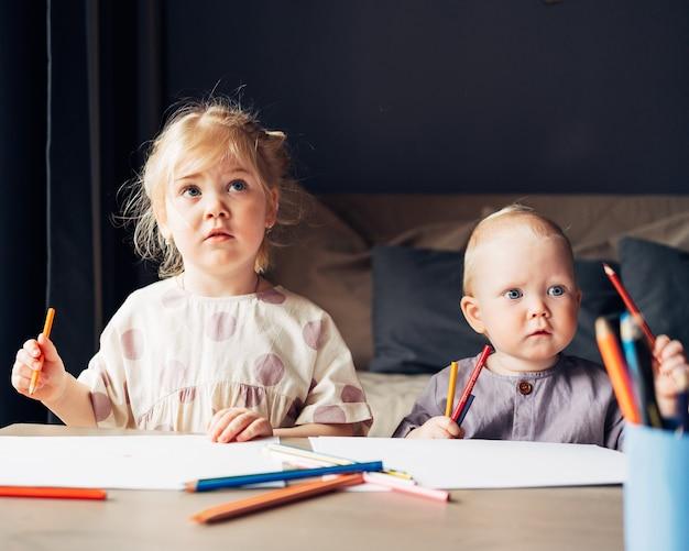 Zwei kinderschwester und babyjungenbruder, die zu hause mit bleistiften zusammen zeichnen