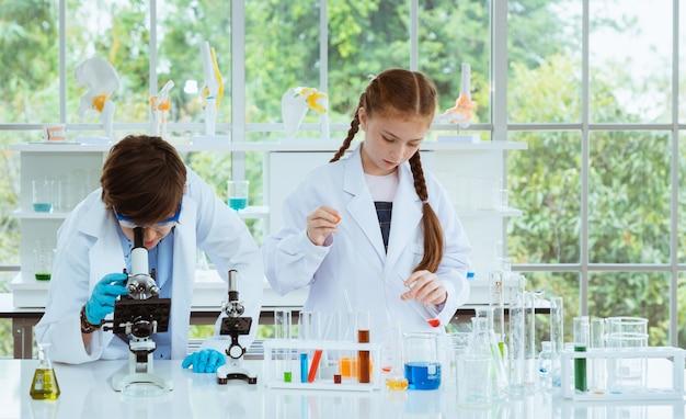 Zwei kinderwissenschaftler, die experimente chemisch mit dem schauen des mikroskops im laborraum machen.