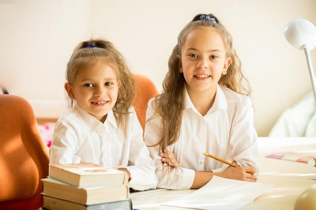 Zwei klassenkameraden sitzen am schreibtisch und lächeln in die kamera