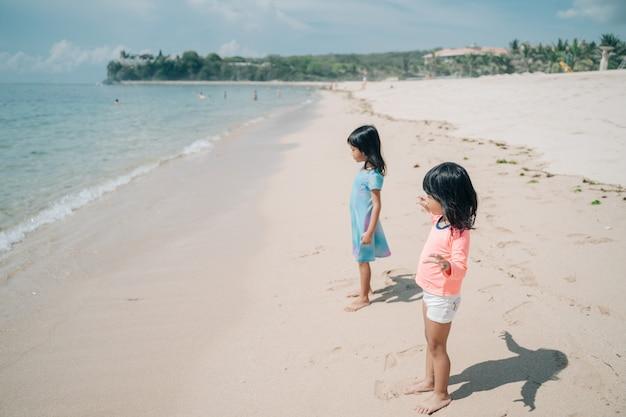 Zwei kleine asiatische mädchen, die am strand spielen