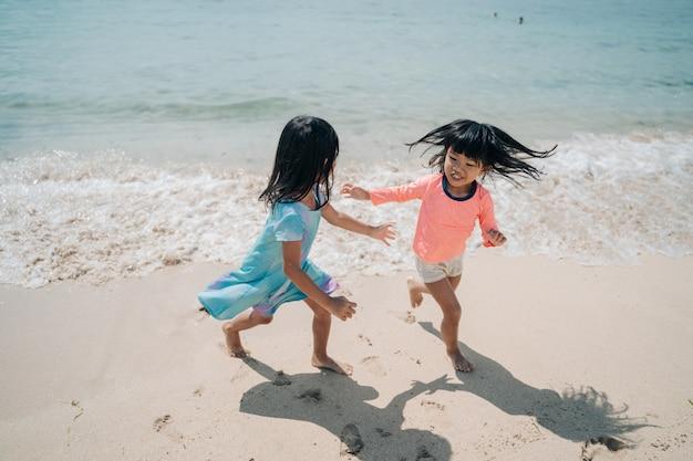 Zwei kleine asiatische mädchen rennen, um den wellen auszuweichen