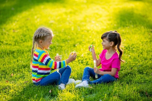 Zwei kleine blonde mädchen und ein brünetter sommer sitzen auf dem rasen und blasen seifenblasen kinder europäischer und indischer abstammung