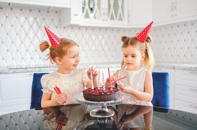 Zwei kleine blonde mädchen von ungefähr fünf jahren in der hellen küche schmücken die geburtstagstorte mit roten und weißen kerzen, geburtstag