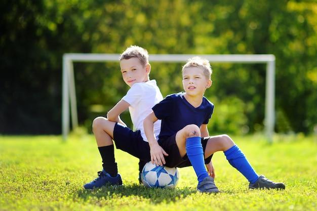 Zwei kleine brüder, die spaß haben, ein fußballspiel am sonnigen sommertag zu spielen