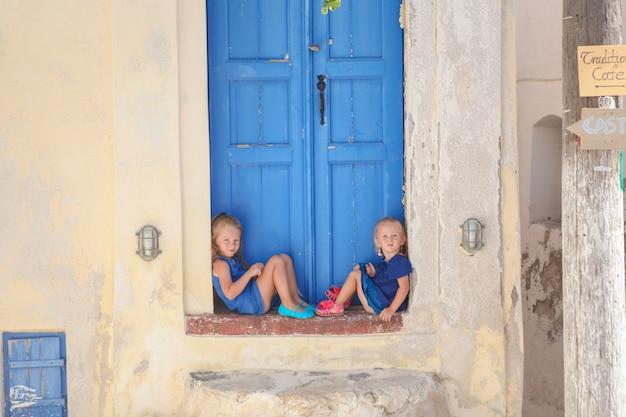 Zwei kleine entzückende mädchen, die auf türschwelle des alten hauses in emporio-dorf, santorini, griechenland sitzen