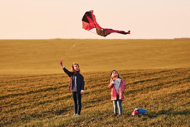 Zwei kleine freundinnen haben spaß zusammen mit drachen und spielzeugauto auf dem feld bei sonnigem tag