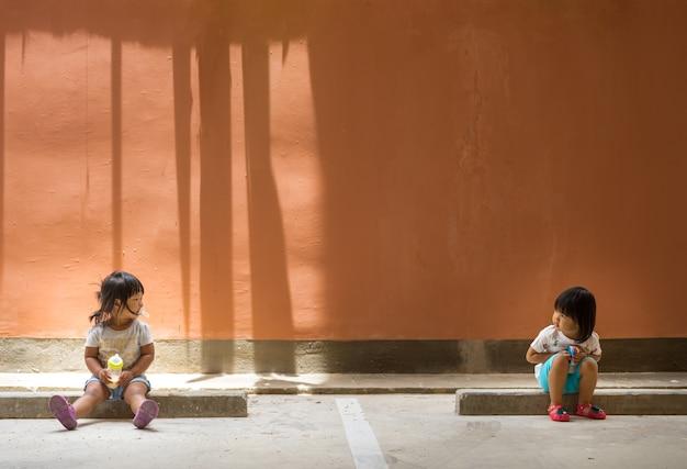 Zwei kleine freundinnen sitzen einander anzusehen