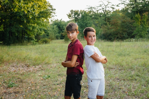 Zwei kleine fröhliche jungs stehen im park und lächeln. glückliche kindheit.