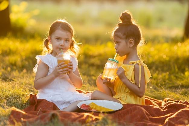Zwei kleine gemischte mädchen trinken smoothies im garten im freien gesunder snack für kinder