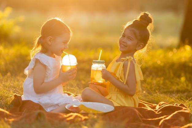 Zwei kleine gemischte mädchen trinken smoothies im garten im freien gvo-freies essen konzept eines gesunden