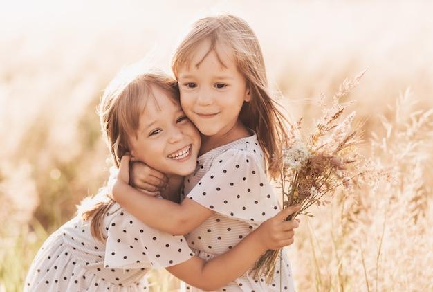 Zwei kleine glückliche eineiige zwillingsmädchen, die im sommer zusammen in der natur spielen. mädchenfreundschaft und jugendkonzept. aktiver lebensstil der kinder.