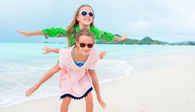 Zwei kleine glückliche mädchen haben viel spaß am tropischen strand, der zusammen spielt