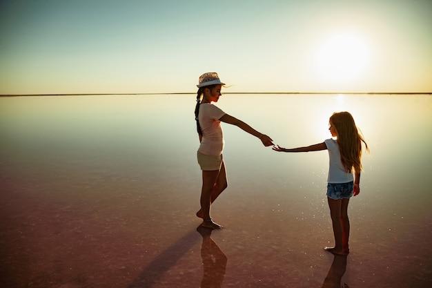 Zwei kleine glückliche schwestern gehen am spiegelrosa see entlang und genießen die warme abendsonne