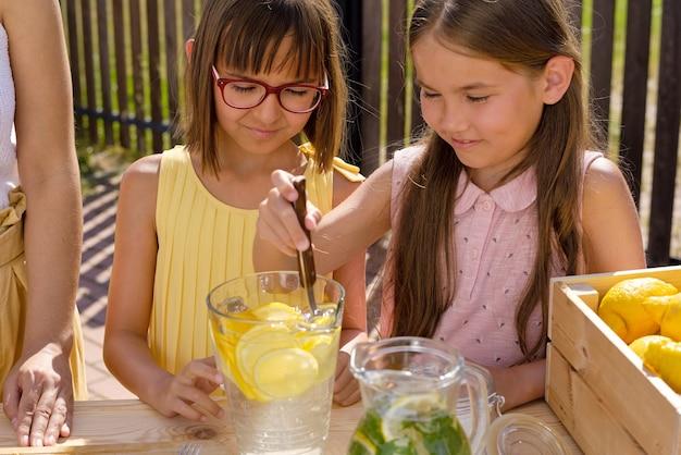 Zwei kleine hübsche mädchen helfen ihrer mutter, frische limonade zum verkauf zu machen, während eines von ihnen zitronenscheibe in krug mit wasser drückt