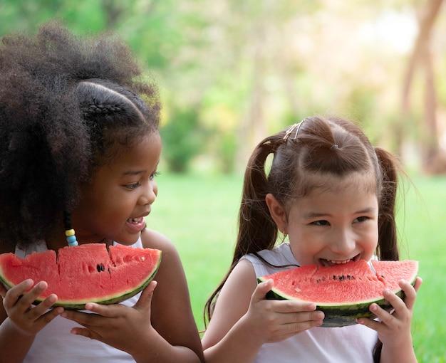 Zwei kleine hübsche mädchen verschiedener ethnischer herkunft, die spaß beim essen von wassermelone im park haben.