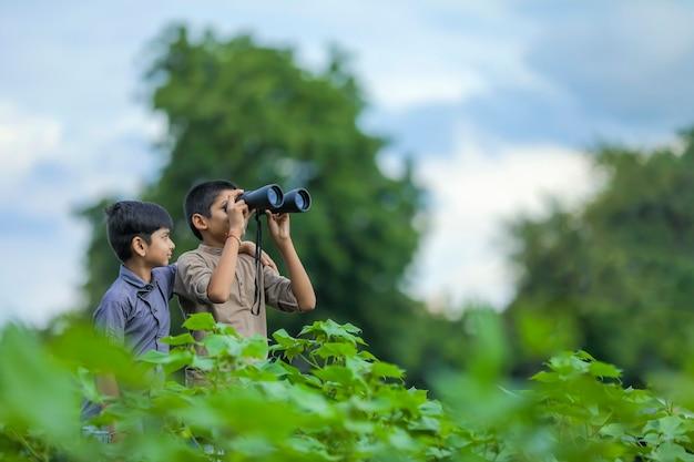Zwei kleine indische jungen genießt in der natur mit einem fernglas