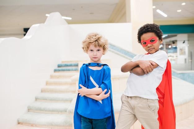 Zwei kleine interkulturelle jungen in kostümen des übermenschen, der sie beim stehen vor der kamera mit spielplatz auf hintergrund betrachtet