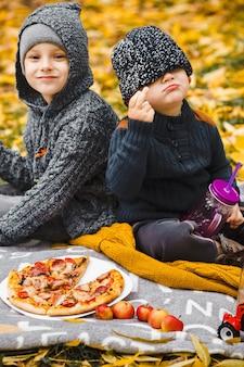 Zwei kleine jungen brüder sitzen auf plaid im park und trinken essen hausgemachte pizza rote äpfel