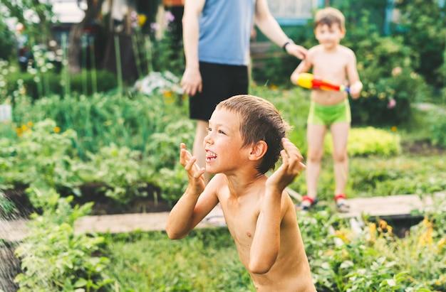 Zwei kleine jungen, die an heißen sommertagen mit wasserpistolen spielen, süße kinder, die spaß mit wasser haben