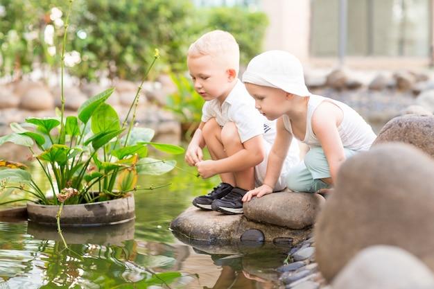 Zwei kleine jungen, die auf steinen in stadt-teich sitzen