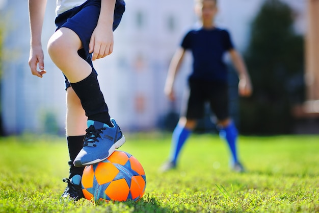 Zwei kleine jungen, die spaß haben, ein fußballspiel am sonnigen sommertag zu spielen