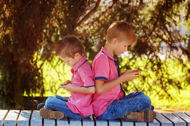 Zwei kleine jungen, die spiele am handy am sonnigen tag spielen, sitt