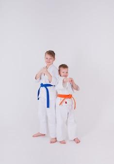 Zwei kleine jungen in einem weißen kimono stehen in einer pose an einer weißen wand