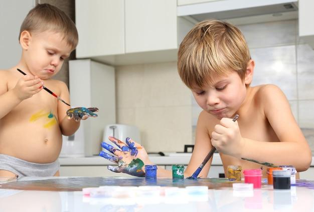 Zwei kleine jungen malen auf einem weißen tisch