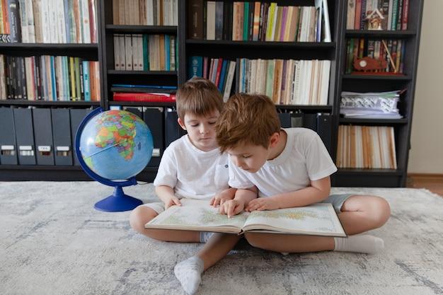 Zwei kleine jungen sitzen zu hause mit globus und erkunden karte, suchen nächstes ziel für reisen