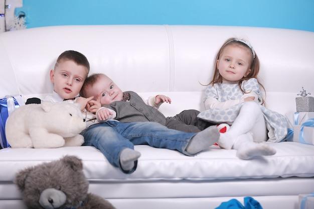Zwei kleine jungen und mädchen, die auf weißem sofa nahe weihnachtsgeschenken sitzen. neujahr. familie, glück, feiertage, weihnachtskonzept.