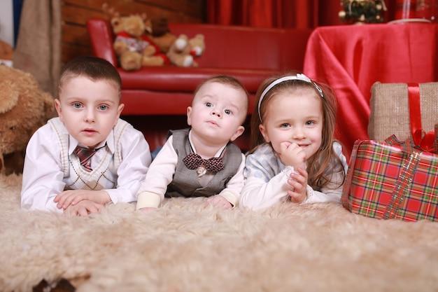 Zwei kleine jungen und mädchen liegen in der nähe eines weihnachtsbaumgeschenks neujahrsfeiertags. familie, glück, feiertage, weihnachtskonzept.